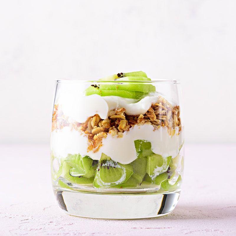 Vaso de cristal con yogurt helado, frutas y muesli
