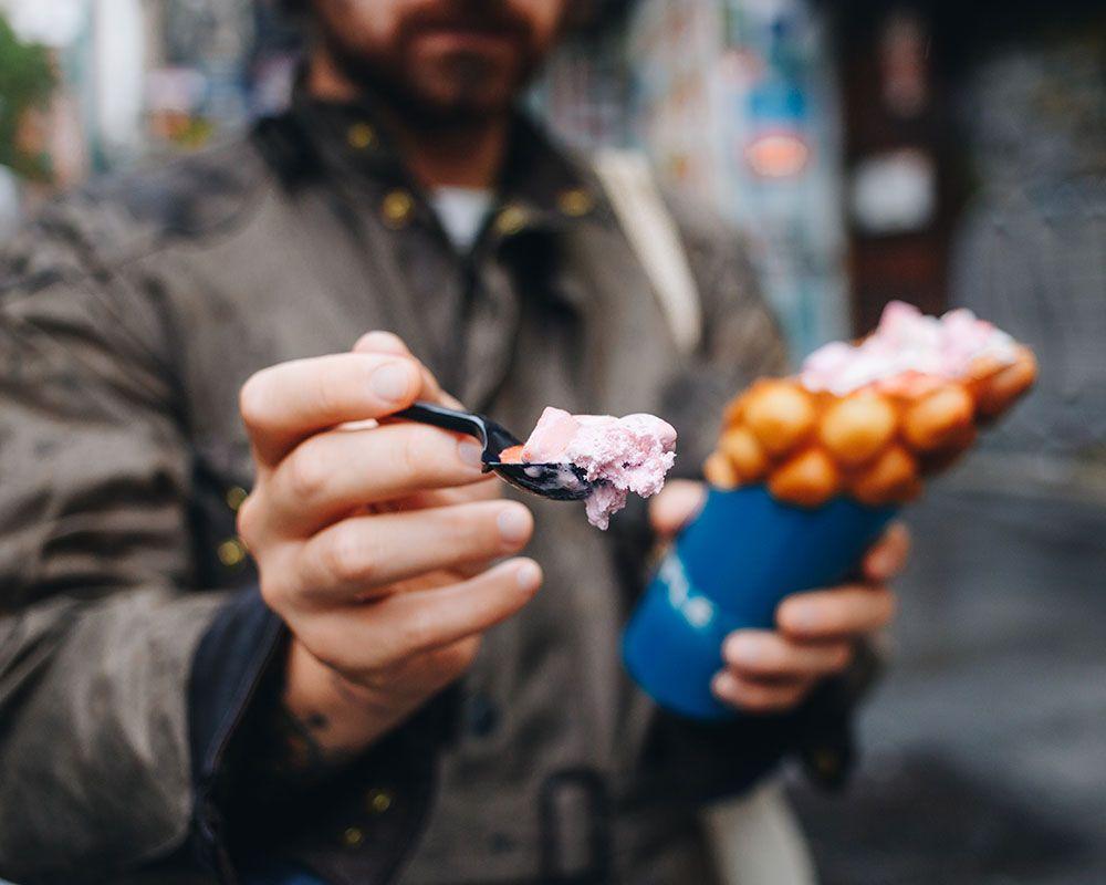 Hombre sujetando un Bubble Waffle con helado de fresa
